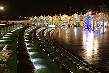 Night view across an open plaza dominated by a long curving water feature that is decoratively lit. At the far side of the plaza there is the arched frontage of a railway station building