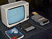 "ZX81 in between a copy of the ""ZX81 BASIC Programming"" manual and a cassette tape recorder, with a black-and-white Ferguson TV set on the background."