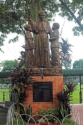 Claret School of Quezon City - Statue of St. Mary Anthony Claret and two schoolchildren in the Claret School of Quezon City.