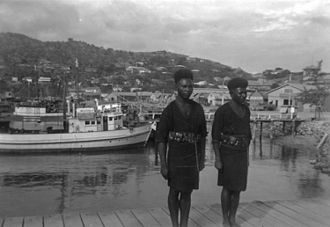Pacific Islands home front during World War II - Clockwise from upper left: Suva (c.1940), ethnic groups of the Pacific Ocean, Papuans at the Port Moresby harbourside (1946), American parade through Auckland