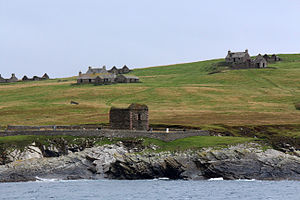 Stroma, Scotland -  alt=View of ruined houses and a ruined building surrounded by a stone wall, located on a green slope leading down to a rocky shoreline