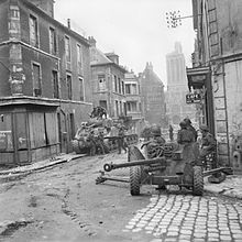 An intersection; an anti-tank gun is covering the crossroads in the foreground and in the street behind are some soldiers and two tanks