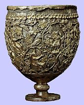 A photo of a large ovoid vessel standing on a short knobbed stem. The cup comprises a silver body enclosed in an openwork layer of gold. The gold ornamentation represents vine scrolls enclosing small seated and praying figures.