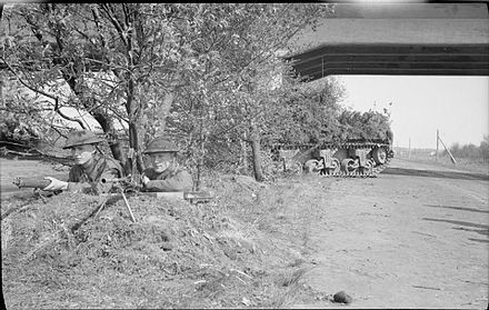 Two Irish Guardsmen and a camouflaged Sherman Firefly guard a section of the Bremen-Hamburg autobahn, 20 April 1945. The British Army in North-west Europe 1944-45 BU4157.jpg