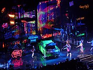 Bird's eye view of a stage, showing large scaffoldings, neon signs and a green car lying in the middle.