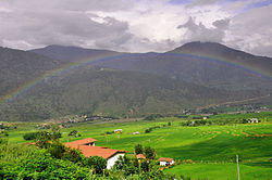 The households in the midst of green paddy field embraced by beautiful rainbow.JPG