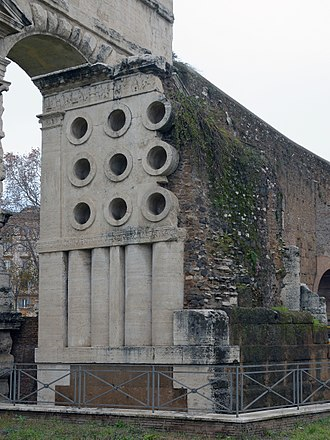 Tomb of Eurysaces the Baker - South facade of the Tomb of Eurysaces outside Porta Maggiore, with the Aqua Claudia behind; the nine cylinders may represent grain measures or mixing vessels