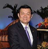 lower half of Truong Tan Sang standing in a dark suit, with a blue tie and white shirt.