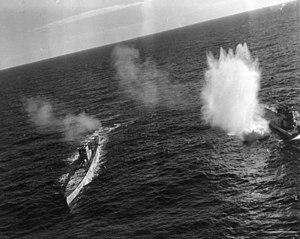 An angled photo of two submarines with bomb splashes around them
