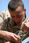 U.S. Marine Corps Pfc. Hector de Jesus, a combat videographer with Headquarters and Headquarters Squadron, handcuffs a simulated hostage after receiving a level 1 oleoresin capsicum contamination April 6, 2010 100406-M-ZN194-007.jpg
