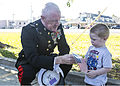 U.S. Marine Lt. Gen. Richard P. Mills, commander of Marine Forces Reserve and Marine Forces North, gives a young boy an American Flag before the start of the Veterans Day parade in the parking lot of Home Depot 131111-M-IJ438-354.jpg