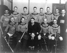 A black and white photo of ice hockey players sitting in two rows on a bench. Their jerseys feature the American flag on the front. Their coach is seated front row, center, with a young boy sitting in front of him.