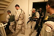 A Border Patrol Special Response Team searches a hotel room-by-room in New Orleans in response to Hurricane Katrina.