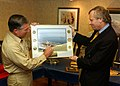 US Navy 040707-N-4757S-055 Rear Adm. Michael Tracy, Commander, Harry S. Truman Carrier Strike Group (CSG), left, presents Secretary General Jaap de Hoop Scheffer, NATO Secretary General, with an official photo of the ship.jpg
