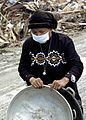 US Navy 050114-N-6817C-190 An elderly woman collects bowls for washing and cooking, near her home, devastated by the Dec. 26 tsunami.jpg