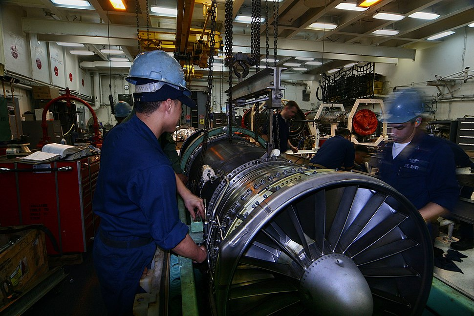 US Navy 050617-N-6009S-001 Sailors assigned to the Aircraft Intermediate Maintenance Department (AIMD) jet shop lower a F-A-18 Hornet engine into its container