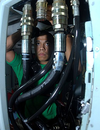 Test fixture - Image: US Navy 070409 N 3038W 002 Aviation Structural Mechanic 3rd Class Rene Tovar adjusts a connection point on a fixture hydraulic supply servo cylinder test station in the hydraulics shop aboard the Nimitz class aircraft carrier U
