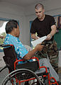 US Navy 070821-N-1467K-024 Tech. Sgt Rayno Boivin, embarked aboard amphibious assault ship USS Peleliu (LHA 5), assists a patient with his paperwork during a medical civic action program at the Tafunsak government building in s.jpg