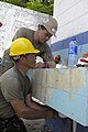US Navy 090625-F-7923S-074 Utilitiesman 2nd Class Carlos Monserrat helps Cabo Santos Jouel Portillo install new pipes for a sink during the renovation of a bathroom at the Club de Leons School.jpg