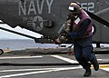 US Navy 101205-N-3620B-048 Aviation Boatswain's Mate (Fuel) Airman Richard Bove moves a JP-5 hose behind the foul line after hot-refueling an MH-53.jpg