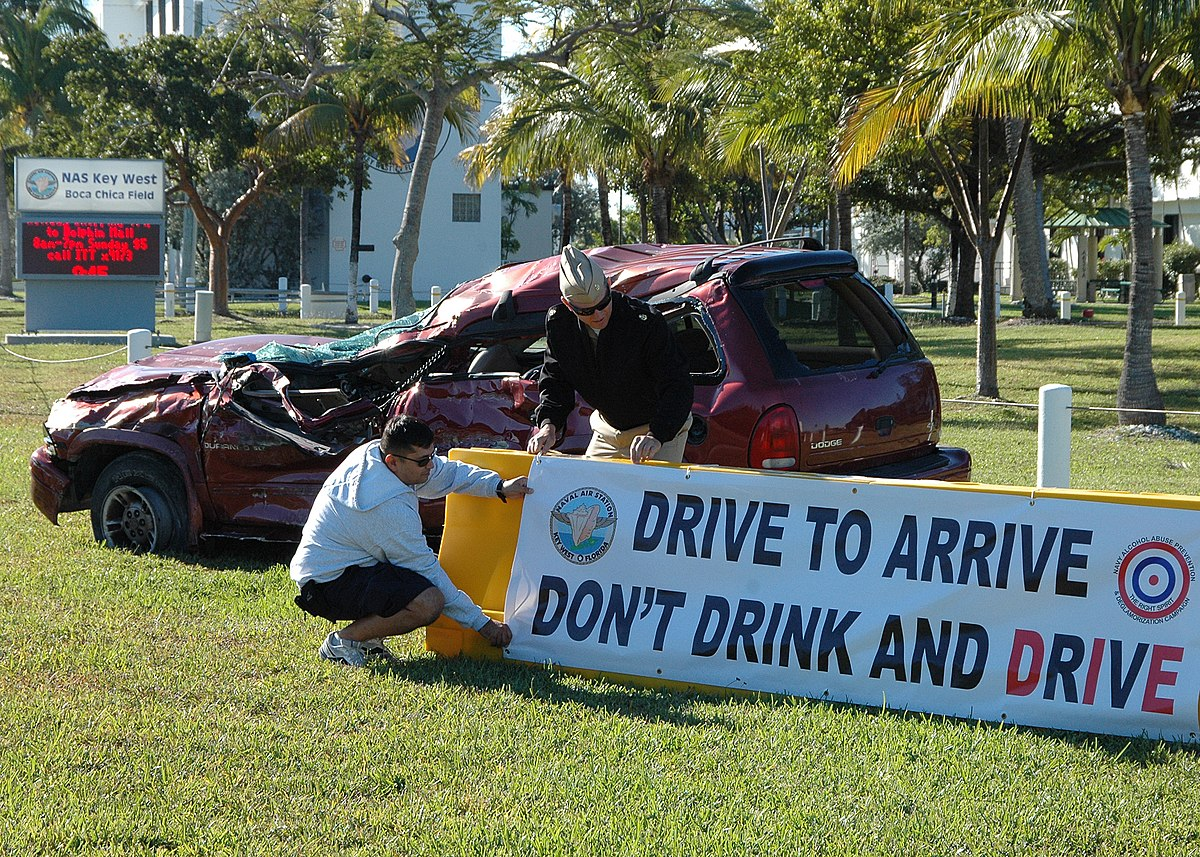 US Navy 101210-N-4779D-021 Command drug and alcohol prevention advisors at Naval Air Station Key West, hang a banner next to a vehicle that crashed.jpg