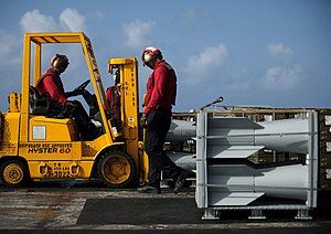 US Navy 111222-N-DR144-084 Aviation Ordnancemen assigned to Weapons Department's G-1 Division position crates of ordnance aboard the Nimitz-class a.jpg