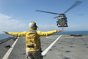 US Navy 120126-N-KS651-086 Boatswain's Mate 3rd Class Allison Mulligan signals an MH-60S Sea Hawk helicopter to land on the flight deck of the amph.jpg