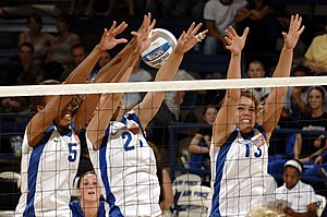 Three volleyball players performing a block