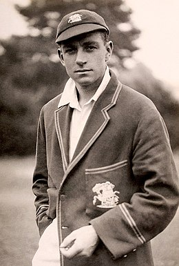 A dark-haired man in a cricket blazer and cap looks at the camera