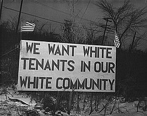 "Housing segregation in the United States - Sign with American flag ""We want white tenants in our white community,"" directly opposite the Sojourner Truth homes, a new U.S. federal housing project in Detroit, Michigan. A riot was caused by white neighbors' attempts to prevent African American tenants from moving in."