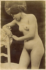 Woman leaning against chair ca. 1890.jpg