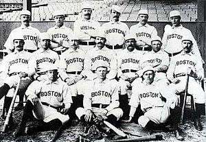 Baseball players are posing for a photograph, six men standing, seven men sitting on chairs, and three are sitting on the ground.
