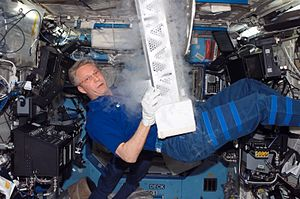Scientific research on the International Space Station - ESA astronaut Thomas Reiter, STS-116 mission specialist, works with the Passive Observatories for Experimental Microbial Systems in Micro-G (POEMS) payload in the Minus Eighty Degree Laboratory Freezer for ISS (MELFI) inside the Destiny laboratory.
