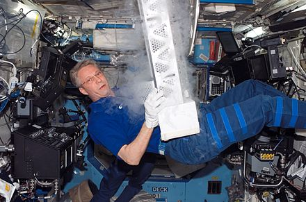 ESA astronaut Thomas Reiter, STS-116 mission specialist, works with the Passive Observatories for Experimental Microbial Systems in Micro-G (POEMS) payload in the Minus Eighty Degree Laboratory Freezer for ISS (MELFI) inside the Destiny laboratory. 382009main MELFI12.jpg