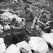 Four men in berets and shirtsleeves in a mortar pit