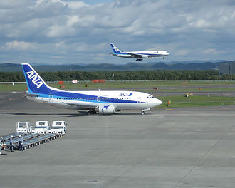 All Nippon Airways - ANA Boeing 737-500 at Sapporo International Airport (Chitose). An ANA Boeing 777-200 can be seen on final approach in the background.