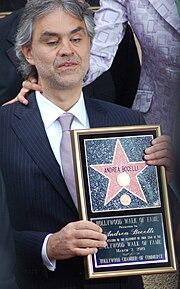 Operkantisto Andrea Bocelli tenas sian plakedon kun ambaŭ manoj ĉe sia 2010 prezentceremonio
