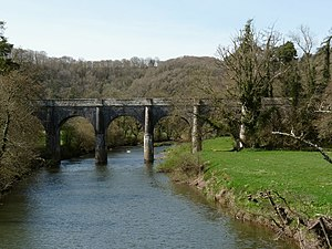 Rolle Canal - Beam Aqueduct, Great Torrington, Devon, viewed from north-east from the old railway bridge (itself now part of the Tarka Trail cycleway). Looking upstream along the River Torridge. This aqueduct carried the Rolle Canal over the River Torridge