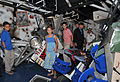 Assistant Secretary of the Navy for Manpower and Reserve Affairs Juan M. Garcia III, second from left, and members of his family walk through one of the simulated bomb-damaged berthing areas on board USS Trayer 120727-N-IK959-690.jpg