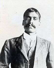 A Bengali hong man with full mustache dressed in dark suit