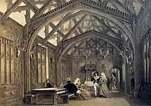 A large room with an arched roof, with the timbers visible. Some people are sitting at a table, and others are standing.