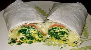Breakfast burrito - A breakfast burrito prepared with cheese, bacon, kale and other ingredients