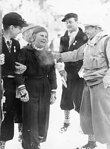 A Scandinavian woman is pictured standing surrounded by three men, one of whom is seen patting her shoulder.