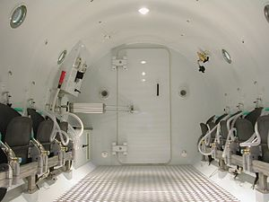 Diving chamber - Internal view of a multiplace chamber for hyperbaric oxygen therapy, showing the airtight door leading to the entry lock.