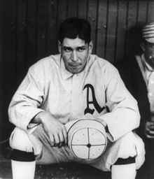 A dark-haired man in a white baseball jersey with a blackletter A on the chest sitting on a bench holding a white cap in his hands