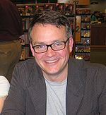 a smiling man wearing glasses faces the camera
