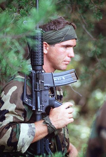 A Sea-Air-Land (SEAL) team member carries his ...