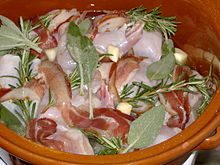 Fette di pancetta avvolgono pezzi di coniglio prima della cottura