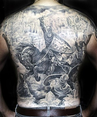 Black-and-gray - Black-and-gray tattoo illustrating The Crusades that encompasses the entire backside.  The shading technique on the shield and other elements is pronounced and creates a sense of depth.