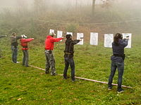 A line of people aiming at targets.